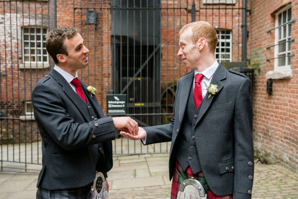 bestman giving the rings to the groom