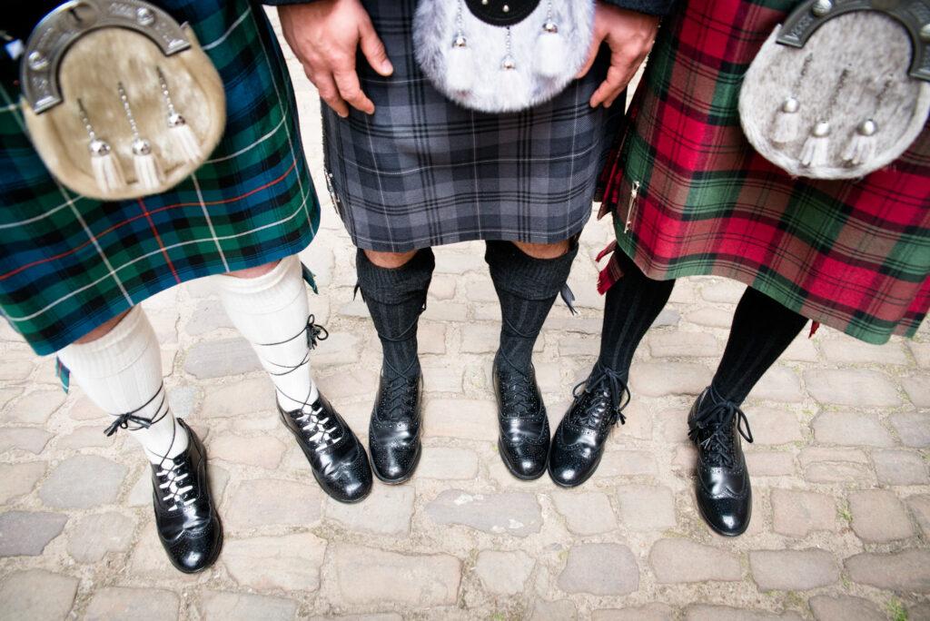 three Scottish men wearing a kilt with different tartans