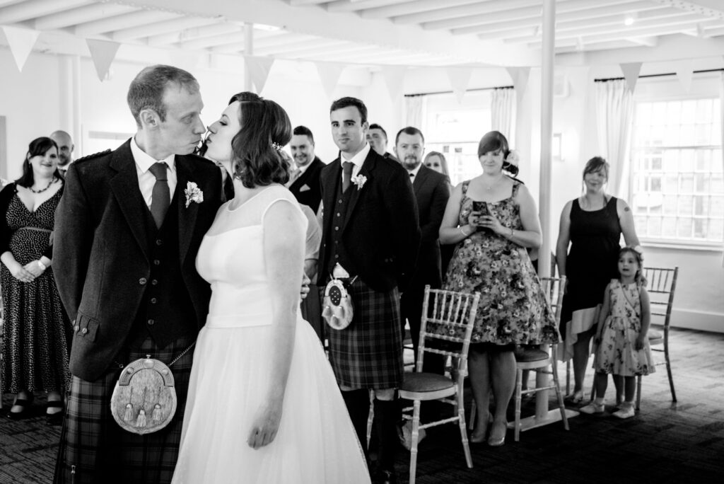 Bride kissing the groom during the ceremony at Quarry Bank Mill