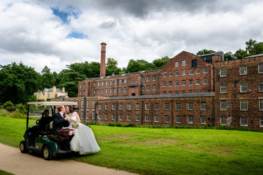 Bride and groom at the back of a golf cart at Quarry Bank Mill