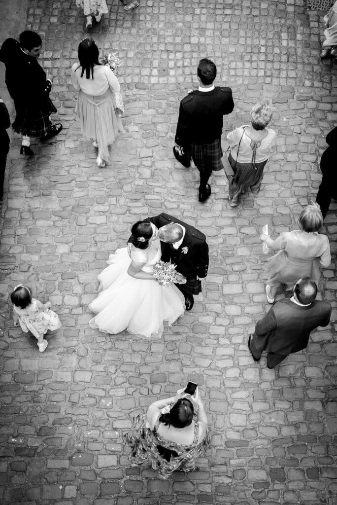 Bride and groom kissing in the middle of the courtyard at Quarry Bank Mill