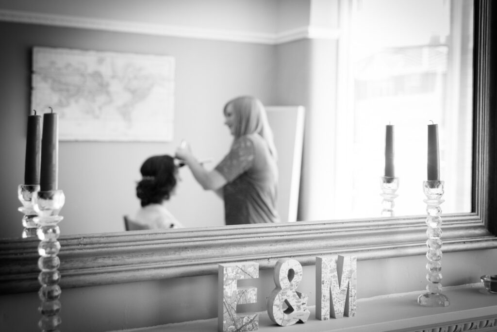 reflection of the bride in the mirror with the make up artist