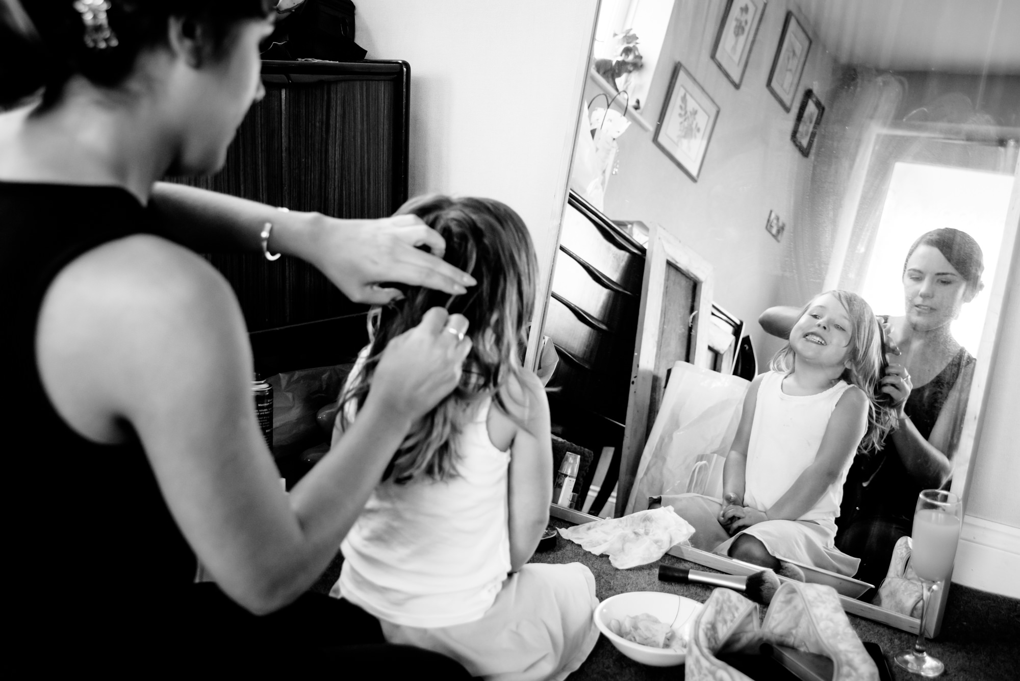 Flower girl having her hair done by a bridesmaid