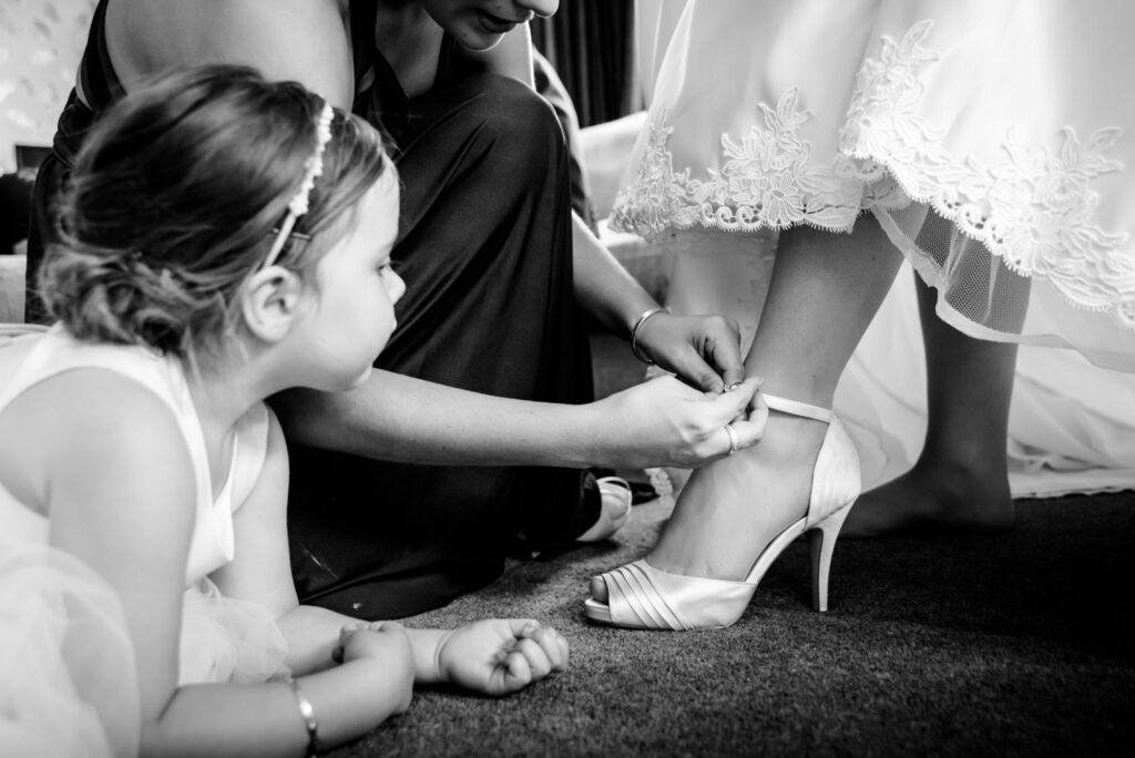 Flower girl watching the bride putting on her shoes