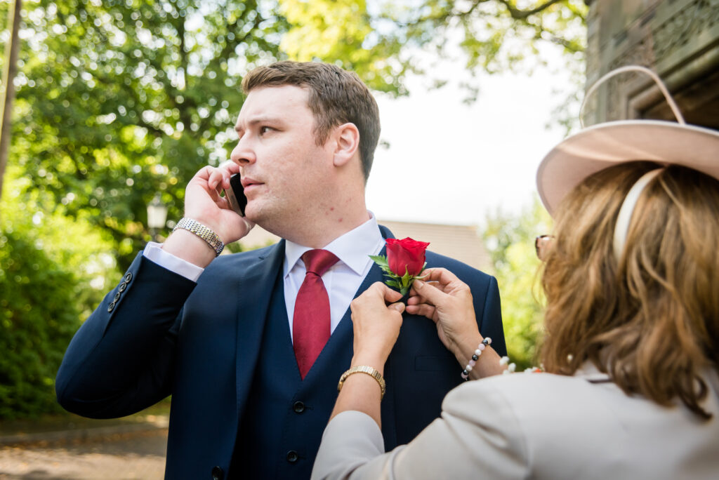 Groom on the phone whilst his mother is fitting the buttonhole