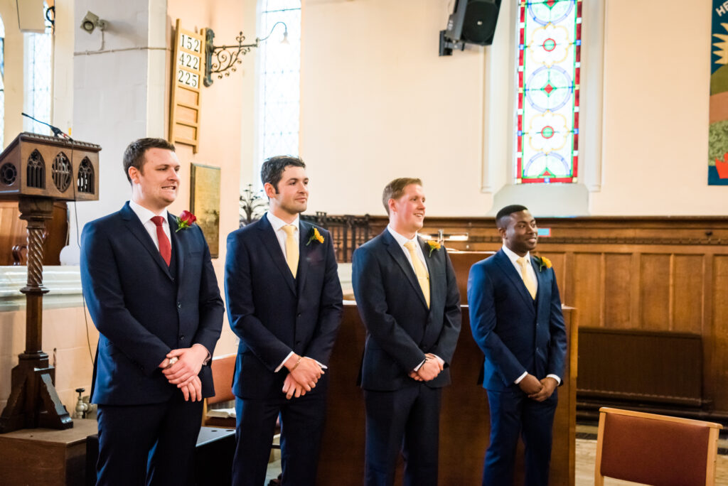 Groom and ushers waiting for the  bride inside St John the Baptist church in Heaton Mersey