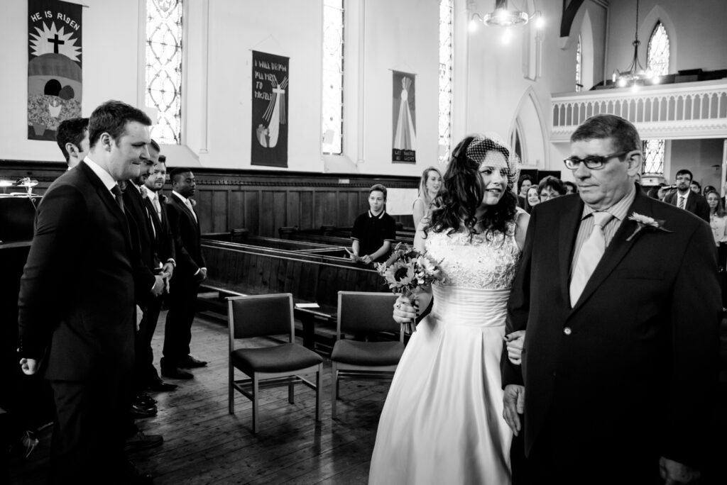 Bride walking down the aisle with her dad at St John the Baptist church in Heaton Mersey