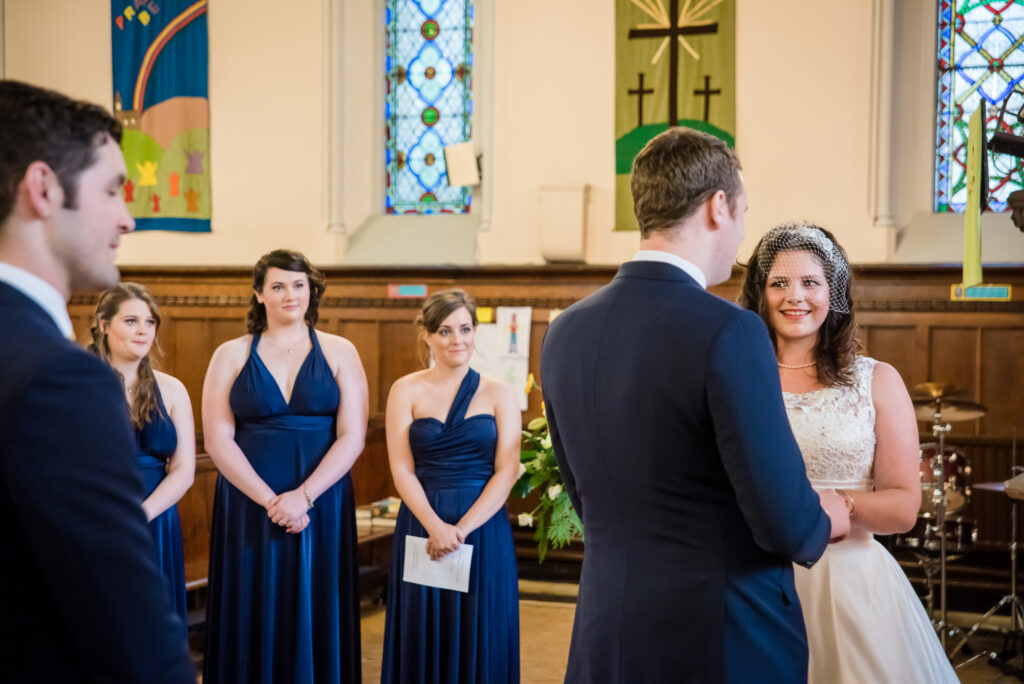 Bride and Groom exchanging vows at St John the Baptist church in Heaton Mersey