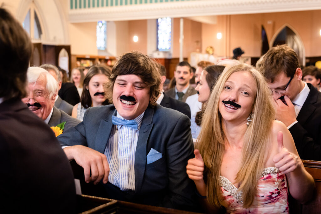 Wedding guests wearing a moustache in church