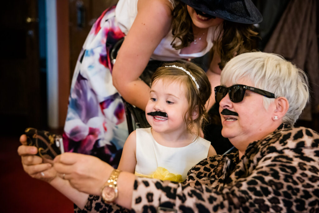 Flower girl and a guest wearing a moustache taking a selfie
