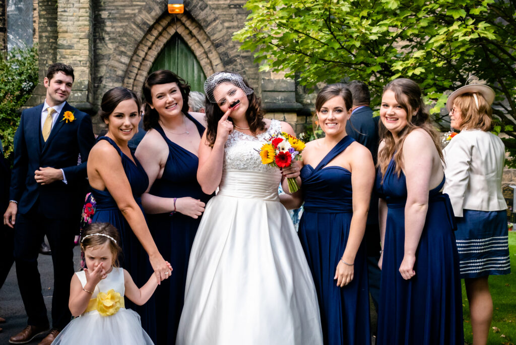 Bride wearing a moustache posing with her bridesmaids