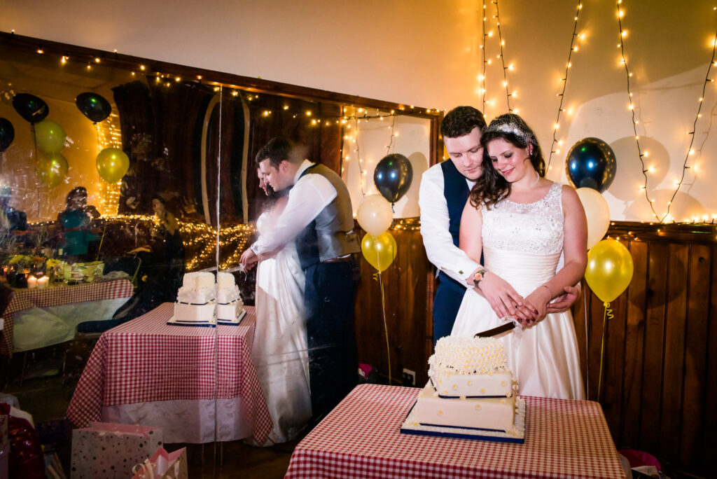 Bride and groom cutting the cake at The Heaton Mersey Community Centre