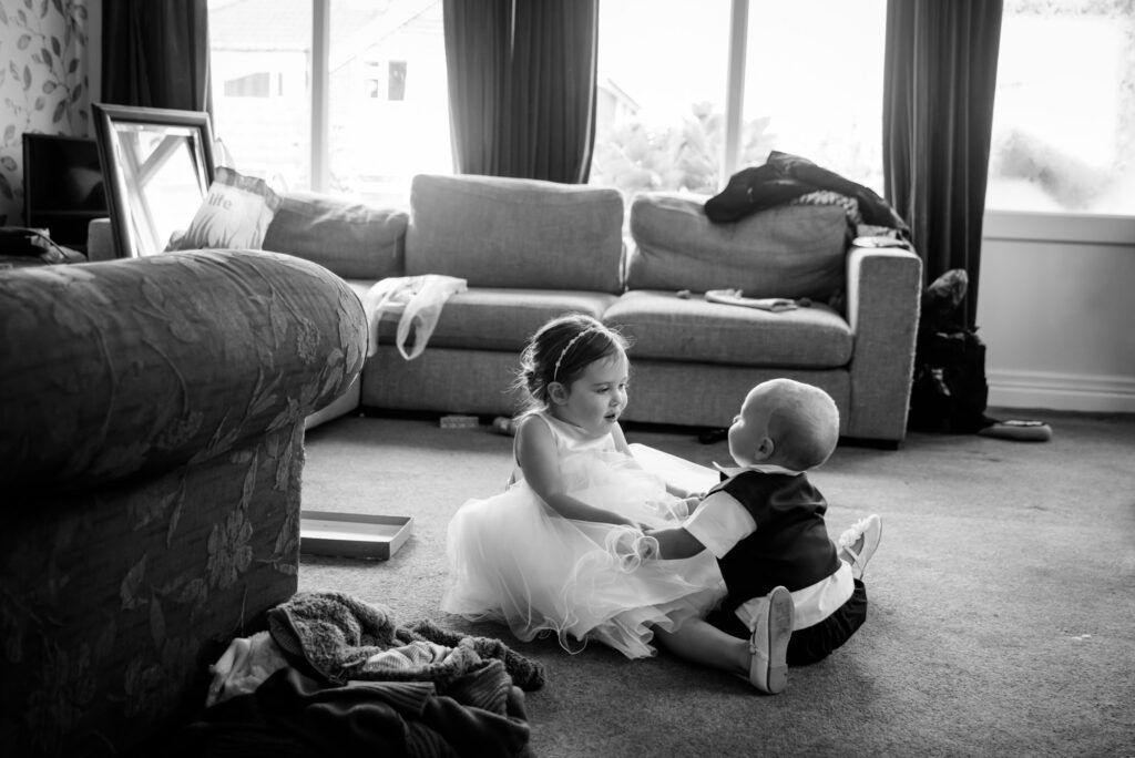 Flower girl and toddler playing during the bridal preparation