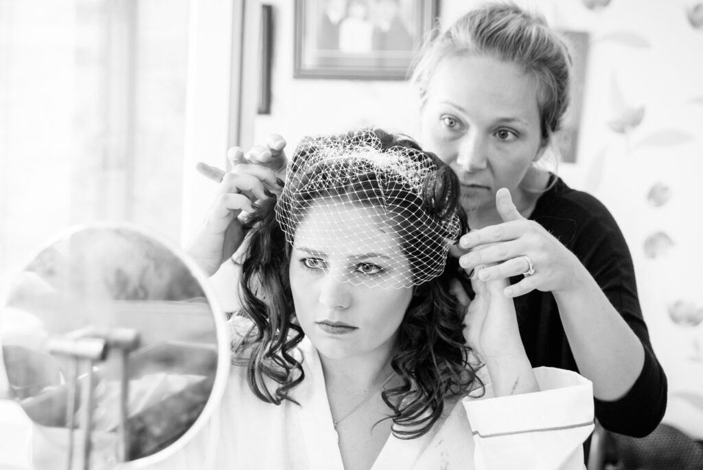 Hairdresser fitting the bride's fascinator