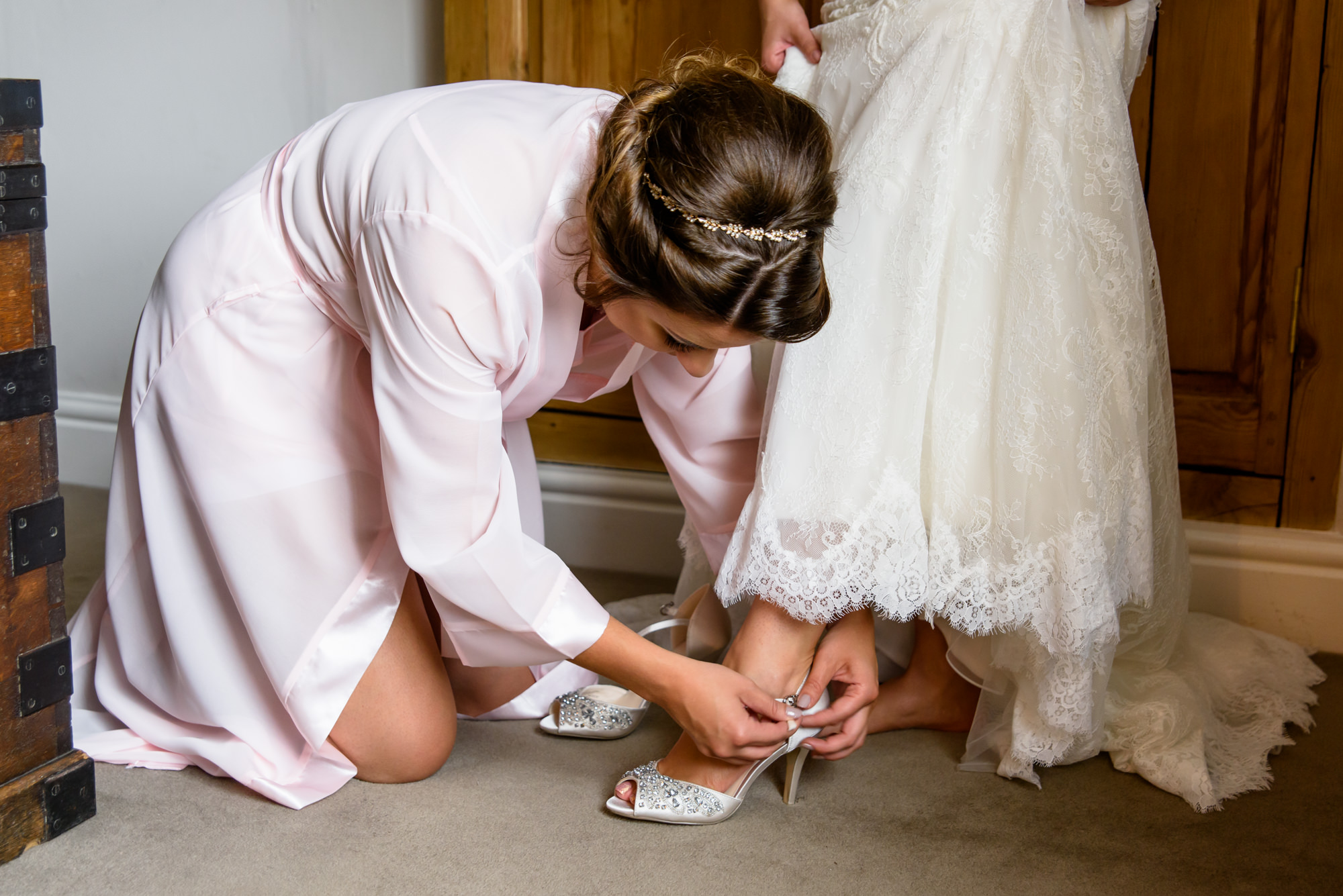 bridesmaid helping to put on the shoes