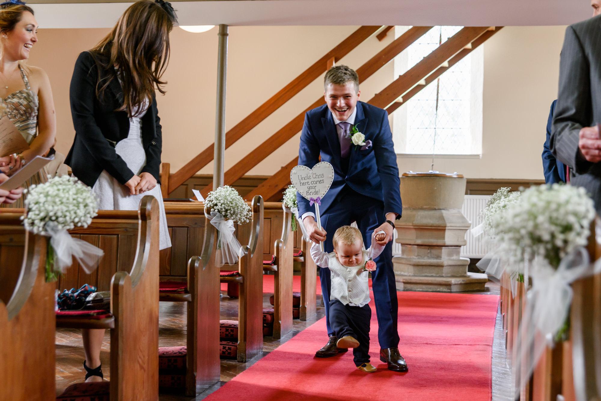 Page boy making an entrance at Parish Church of Saint Michael Whitewell