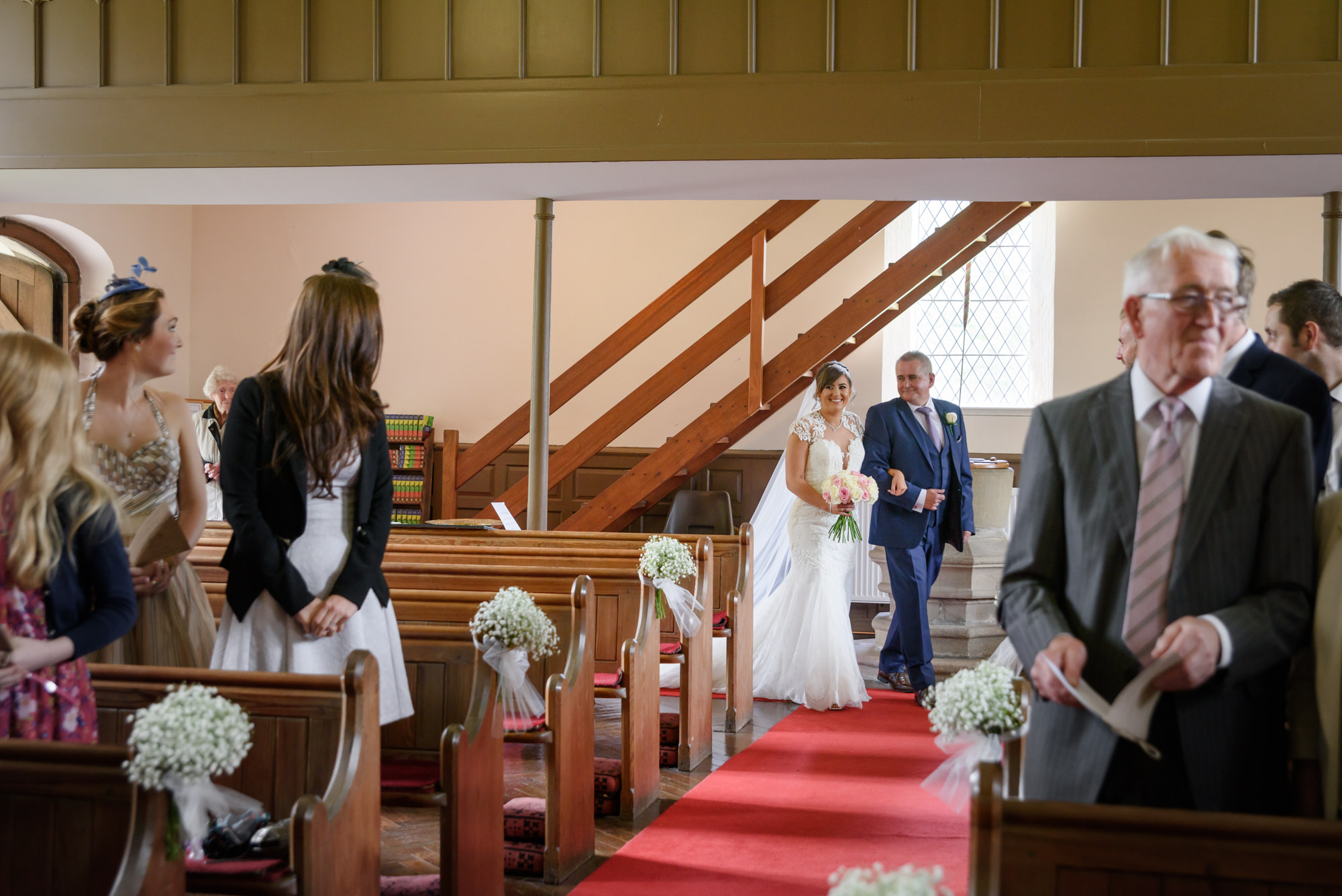 Bride walking down the aisle at the Parish Church of Saint Michael Whitewell
