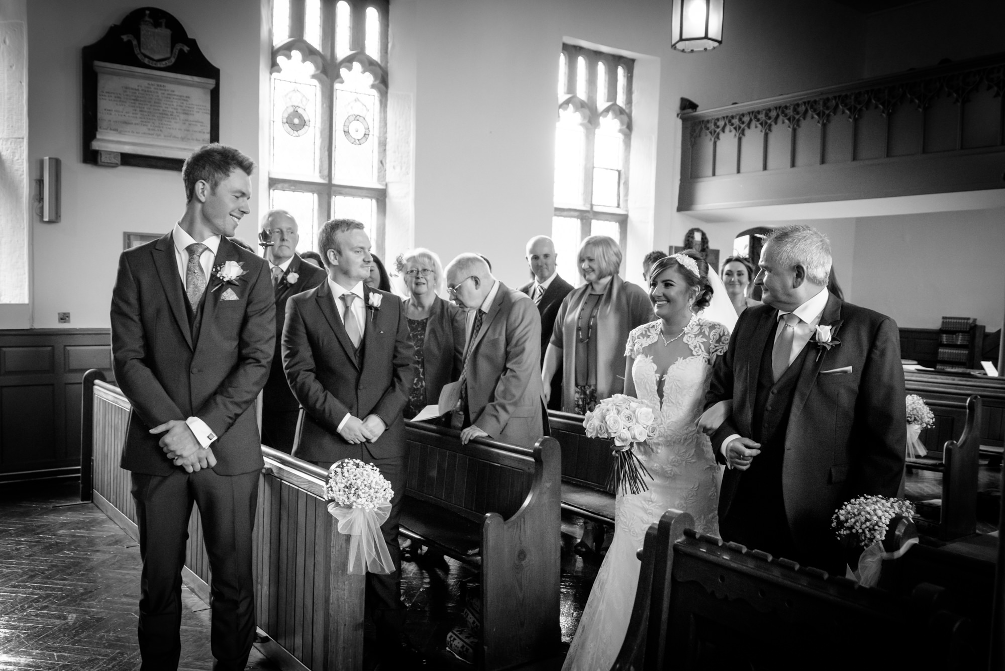 Bride meets the groom down the ailse at the Parish Church of Saint Michael Whitewell