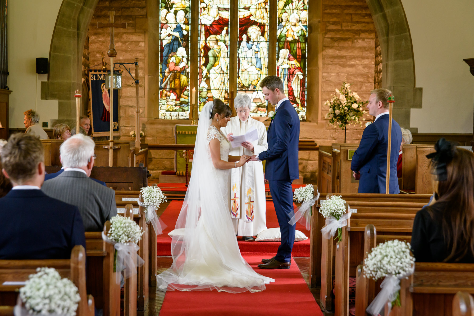 Bride and groom exchanging the rings at the Parish Church of Saint Michael Whitewell