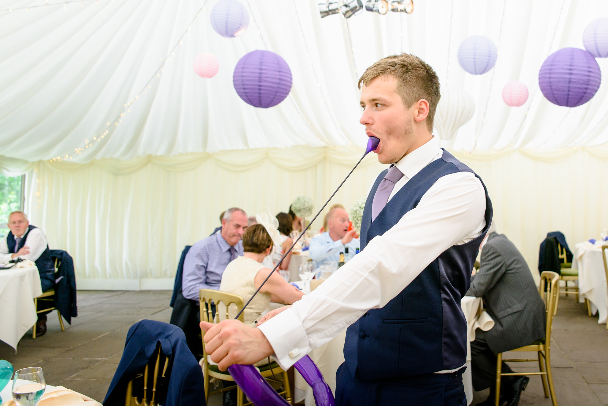wedding guest trying to make a dog with a balloon