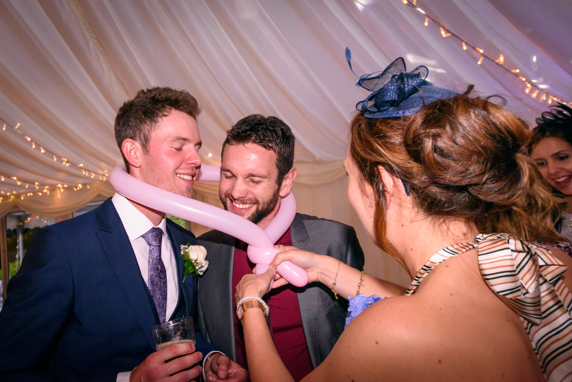 Groom and a guest being tied together with a balloon