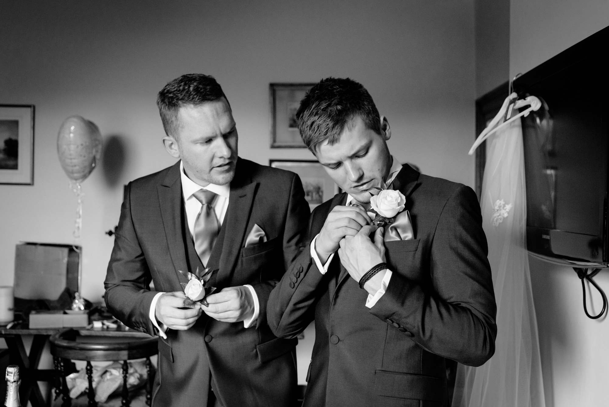 Groomsmen putting on the buttonhole flower