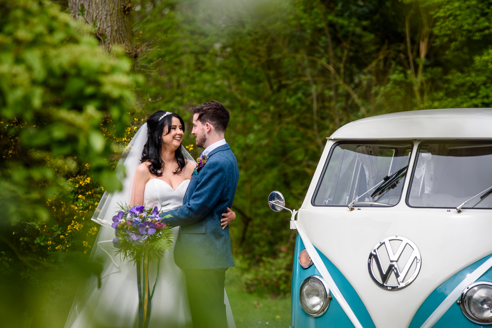 Bride and groom posing in front of the camper van