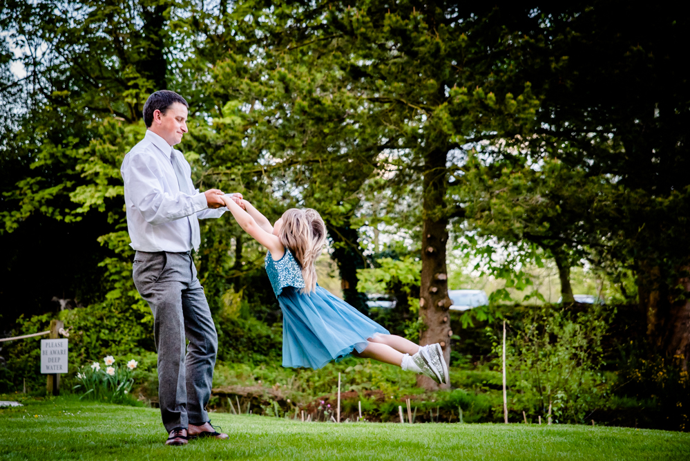 A guest spinning a child during the wedding reception at Oak Tree of Peover