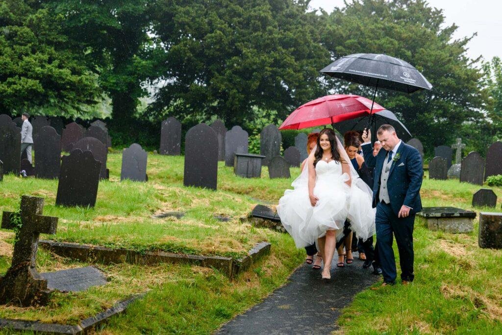 Bride in the rain at st mary's church in Llanfairpwllgwyngyll