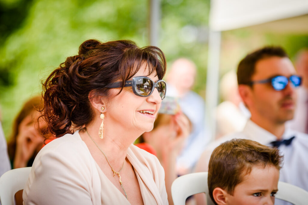 Mother of the bride with reflection of ceremony in her sunglasses
