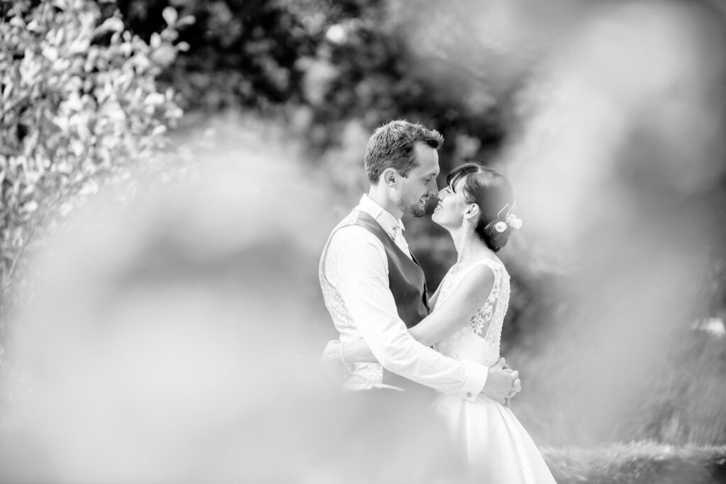 bride and groom photographed through the flowers