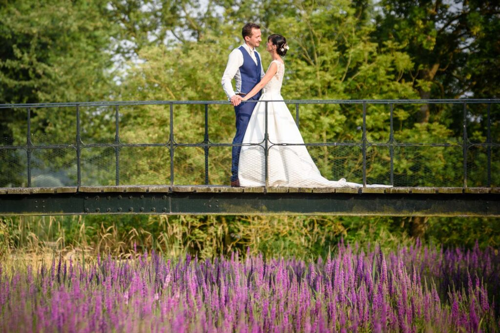 Bride and groom portrait on a bridge over purple flowers