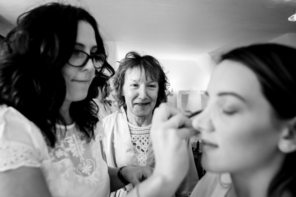 Mum looking at bride having makeup done
