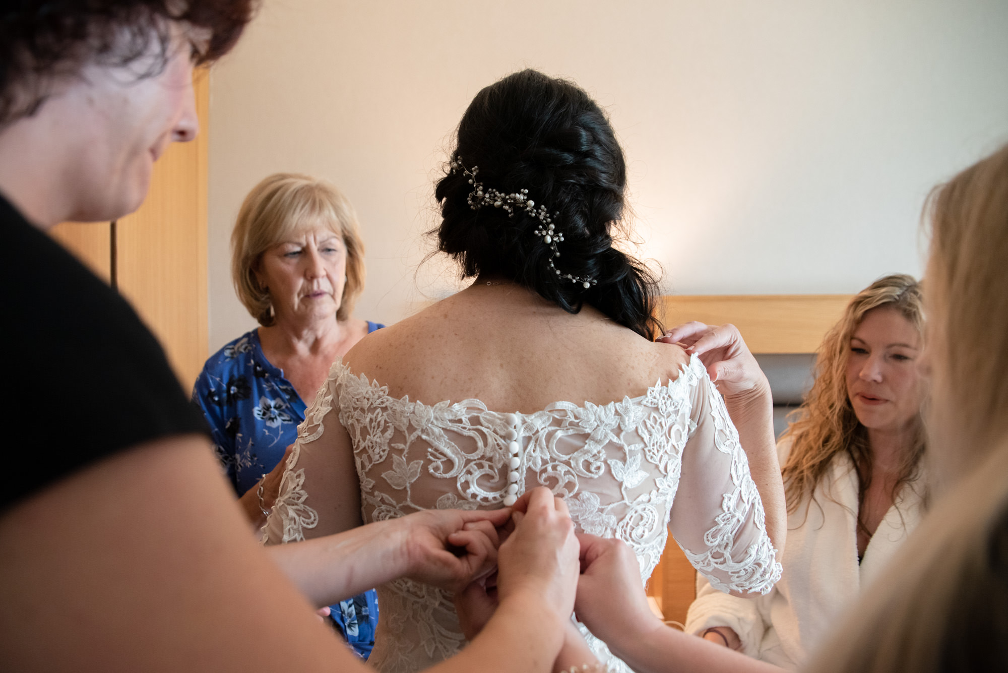 Buttoning up the bride's dress