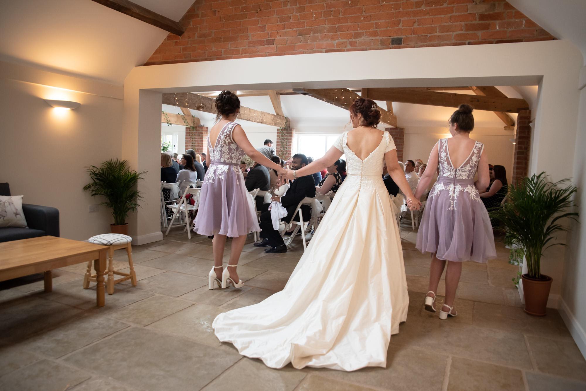 Bride walking through the roost of Hanbury Wedding Barn