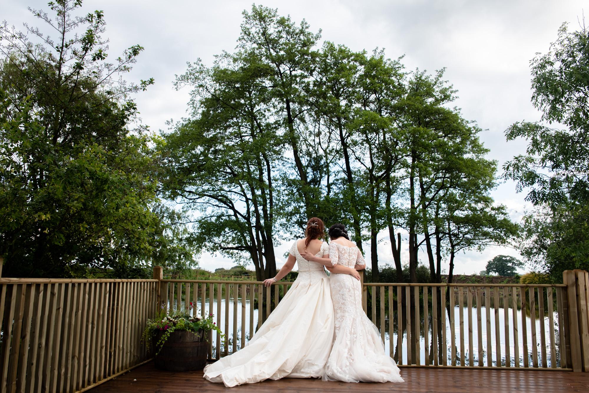 Two brides enjoying the lake view at Hanbury Wedding Barn
