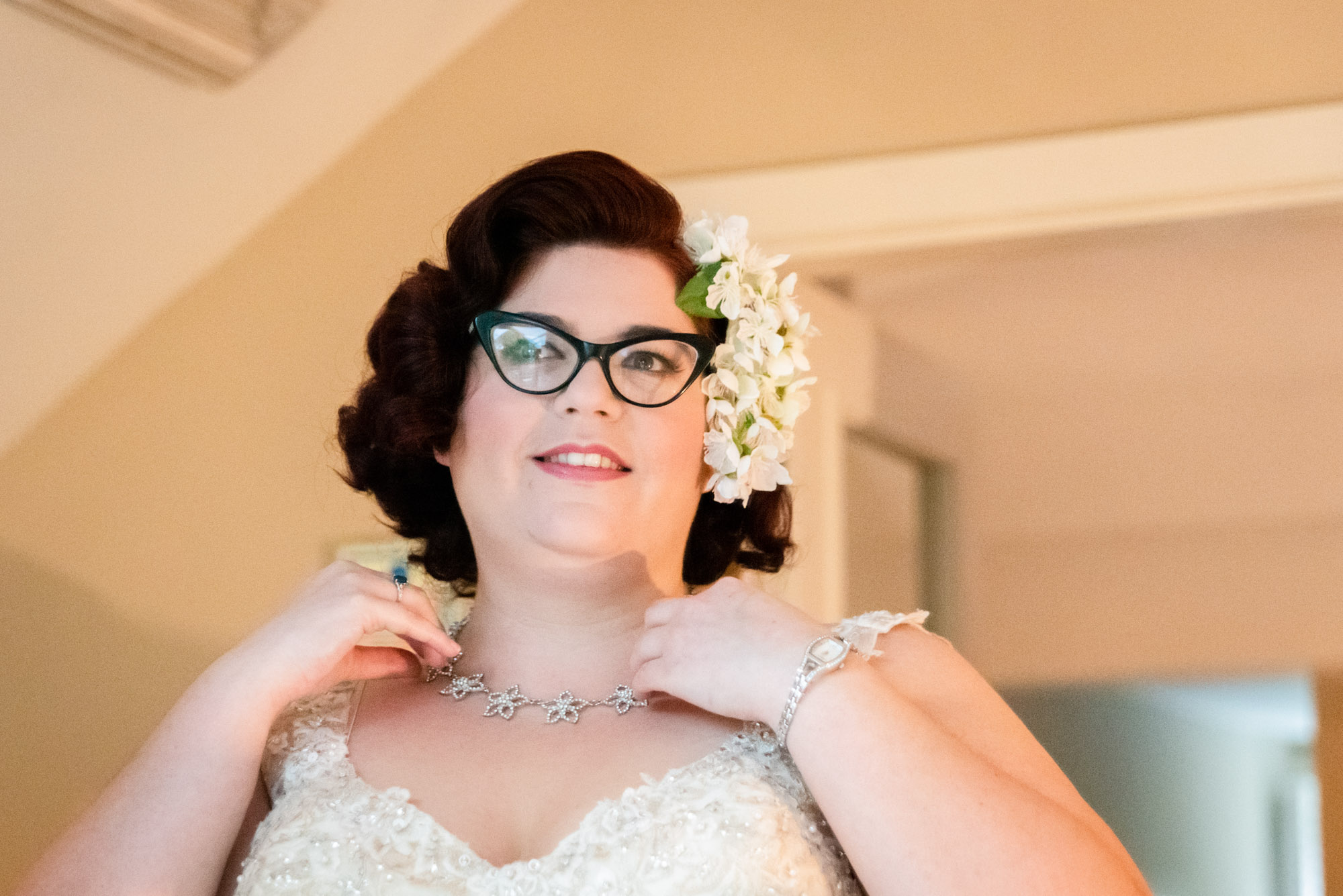 bride putting neckless on