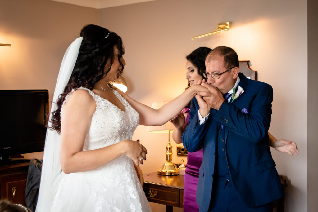 father kissing the bride hand
