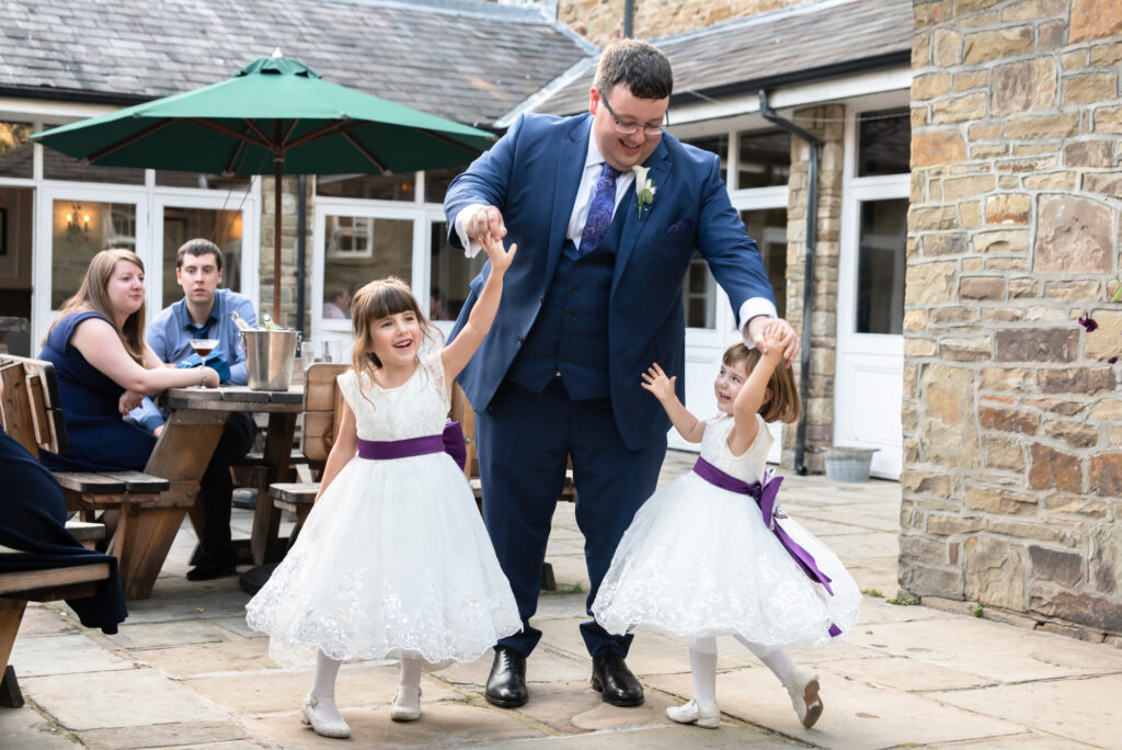 groom spinning the flower girls