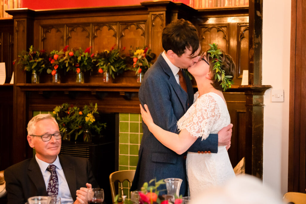 Bride and groom kissing during speeches