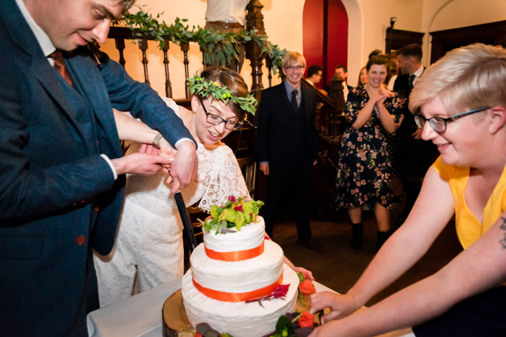 cutting the cake with help from a bridesmaid