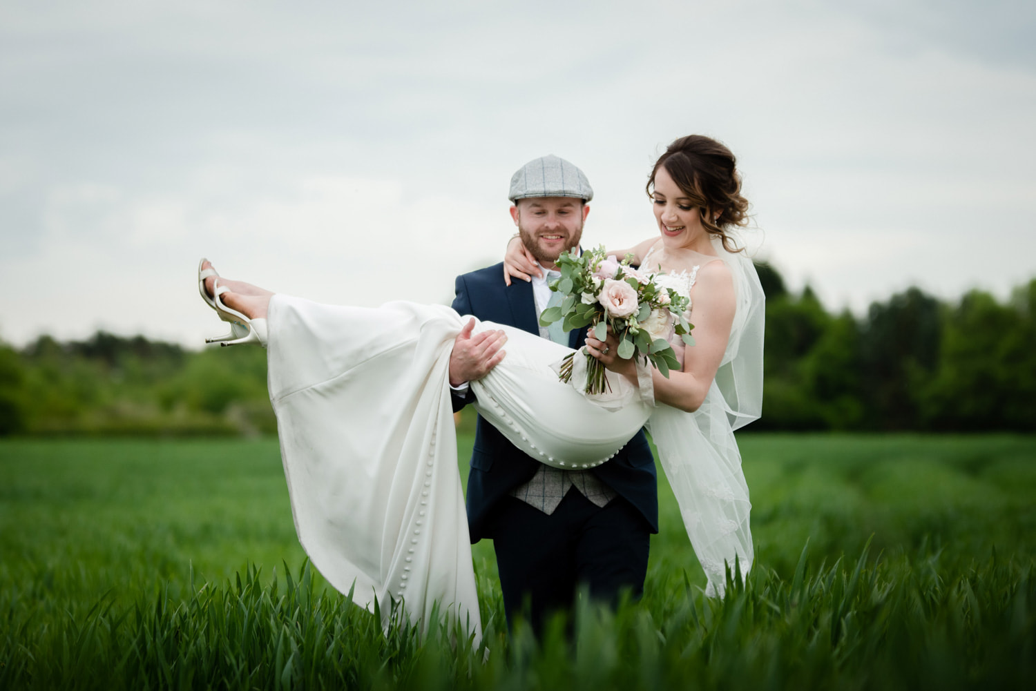 Groom carrying the bride in a field