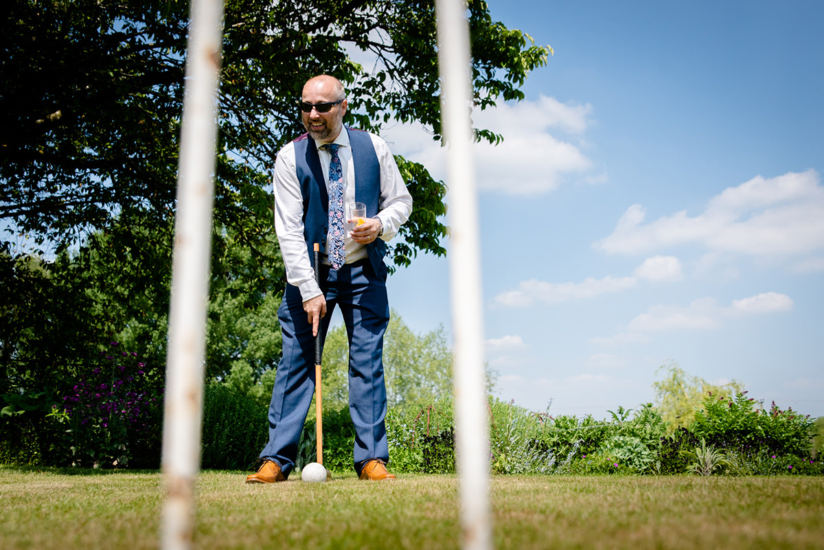 Wedding guest playing croquet whilst holding his beer