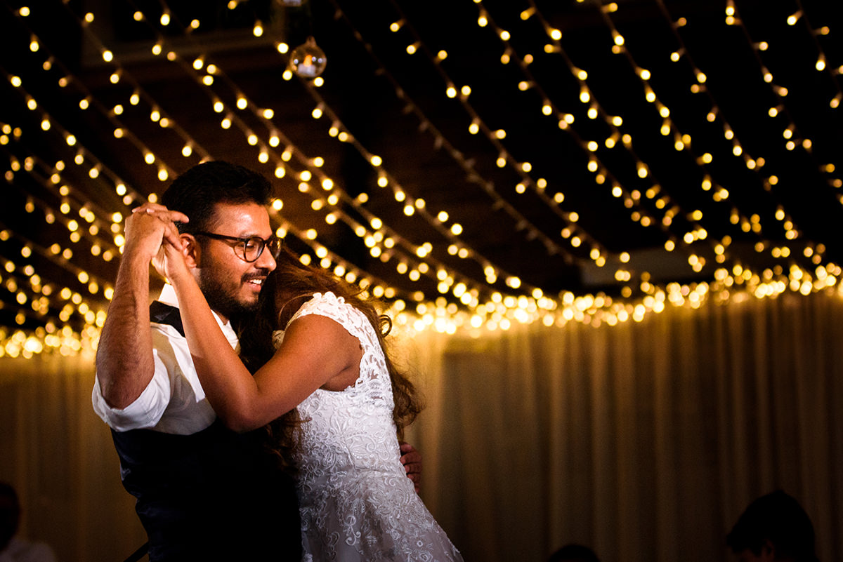 Bride and groom dancing under the fairy lights