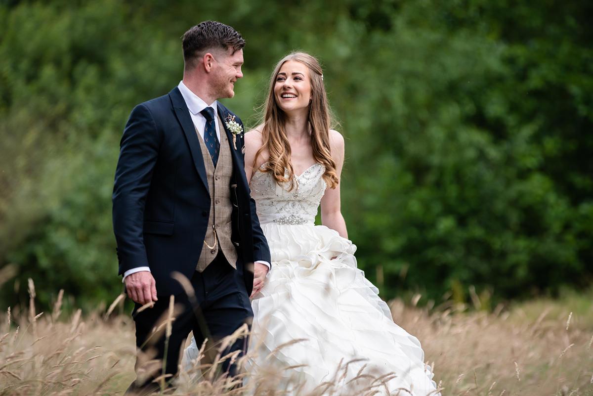 Bride and groom walking in a wheat field