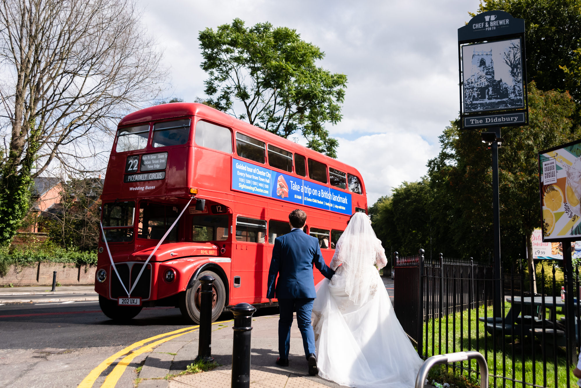 Bride and groom walking towards the red double decker bus they hired