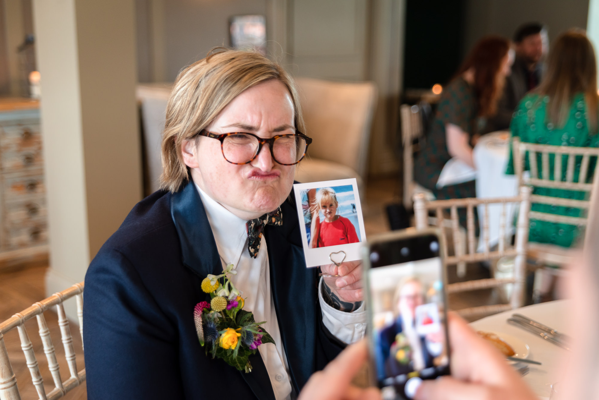 Bride pulling a face while showing a photos of herself