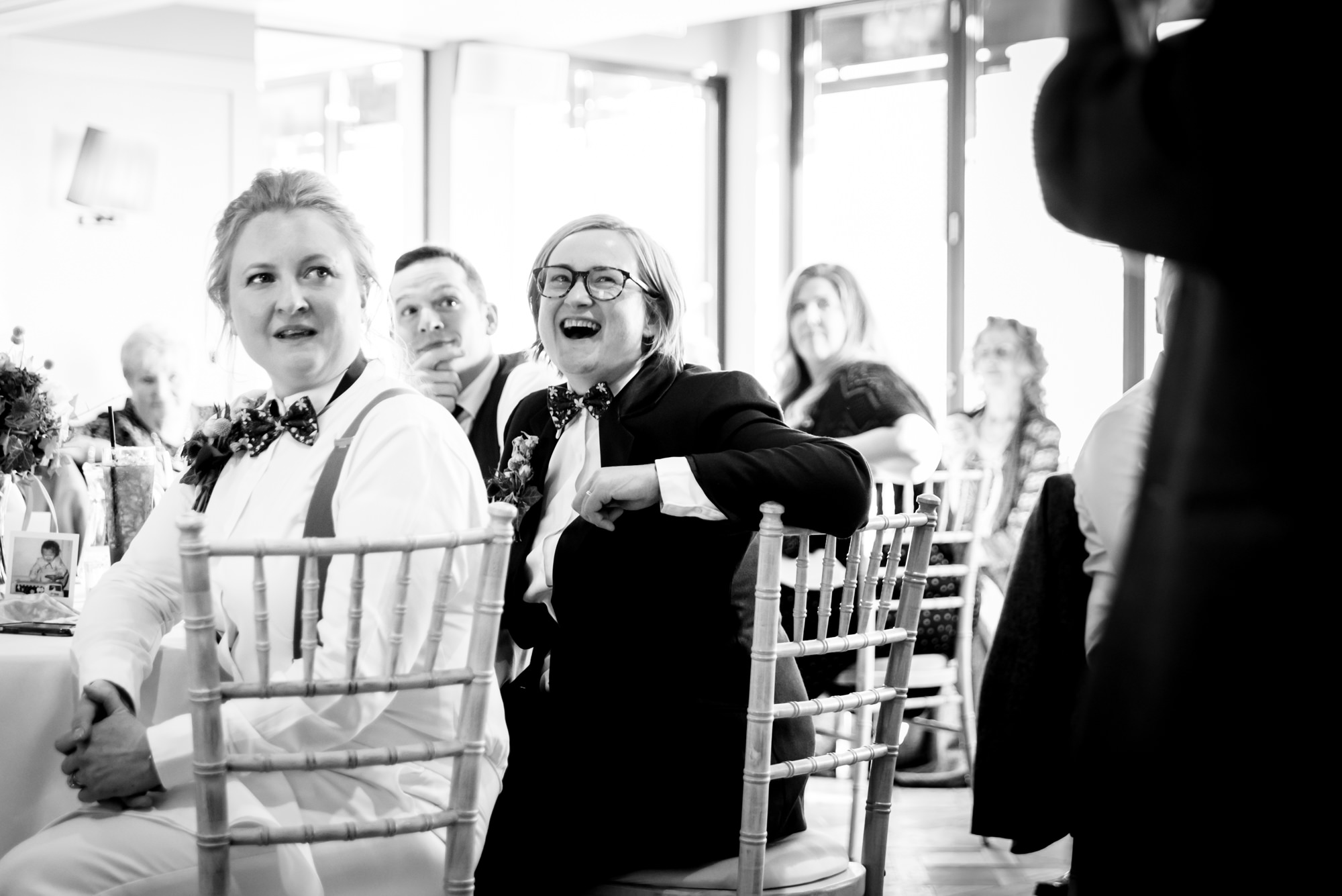 One bride is looking horrified while the other one is laughing