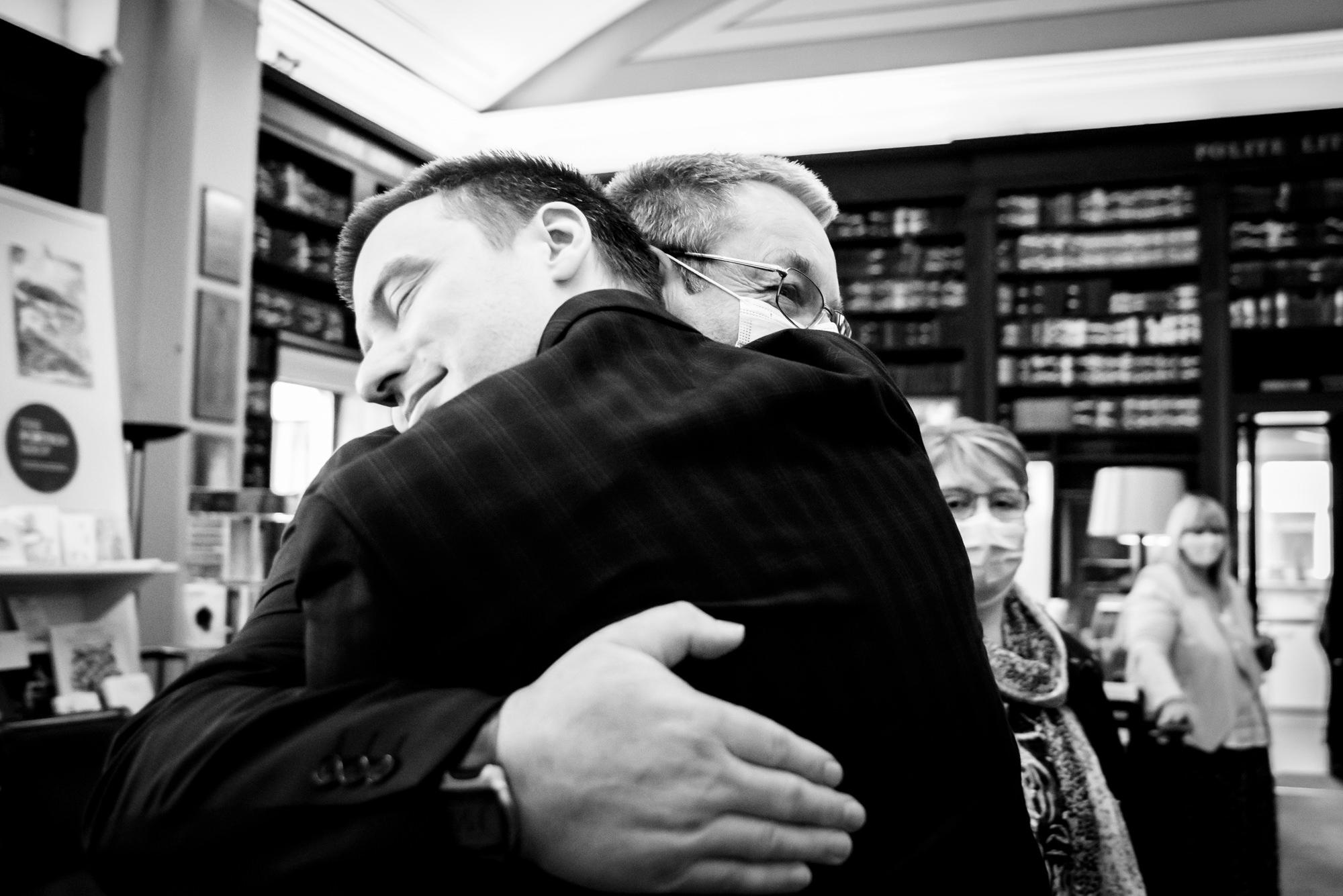 Groom hugging dad