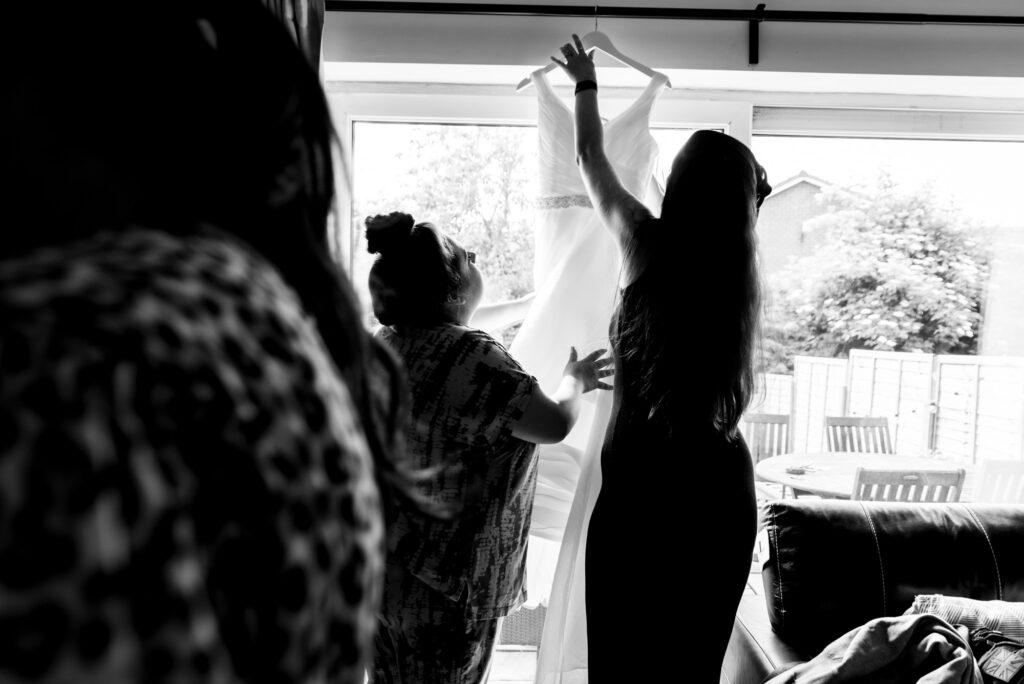Bridesmaids hanging the dress